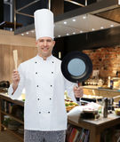 Happy male chef holding frying pan and spatula. Cooking, profession and people concept - happy male chef cook holding frying pan and spatula over restaurant Royalty Free Stock Photo