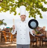Happy male chef holding frying pan and spatula Stock Photography