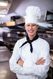 Happy male chef standing with arms crossed in kitchen Stock Image