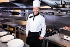 Happy male chef standing in kitchen. Portrait of happy male chef standing in kitchen stock photo