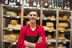 Happy male clerk standing against shelves in cheese shore Stock Photography