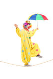 Happy male clown with umbrella walking on a rope. Full length portrait of a happy male clown with umbrella walking on a rope  on white background Royalty Free Stock Photography