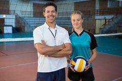 Happy male coach and volleyball player standing in the court. Portrait of happy male coach and volleyball player standing in the court Stock Photos