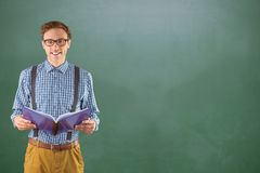 Happy male college student holding book while standing against chalkboard royalty free stock photos