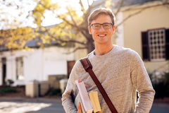 Happy male college student outdoors. With books. Young university student with books in campus royalty free stock image