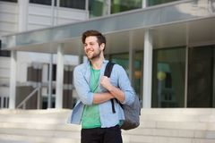 Happy male college student standing outside with bag. Portrait of a happy male college student standing outside with bag Stock Photo