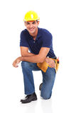 Male constructor kneeling. Happy male constructor kneeling over white background Royalty Free Stock Photos
