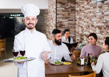 Happy male cook showing country restaurant. To visitors Stock Images