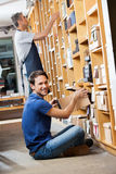Happy Male Customer Removing Box From Shelf In Stock Photos