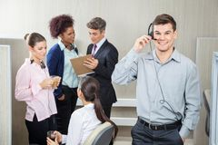 Happy Male Customer Service Representative Using. Headphones with team discussing in background at call center Stock Photo