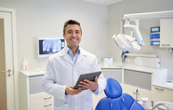 Happy male dentist with tablet pc at dental clinic Stock Images
