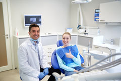Happy male dentist with woman patient at clinic Royalty Free Stock Image