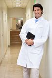 Happy Male Doctor Holding Book. Portrait of a happy mixed race male doctor holding book while standing in hospital passageway Stock Photography
