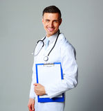 Happy male doctor holding empty clipboard Royalty Free Stock Images