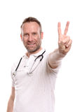 Happy male doctor making a victory gesture Royalty Free Stock Photos
