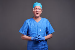 A happy male doctor. A happy middle aged male doctor standing in blue scrubs and rubber gloves and laughingr Stock Images