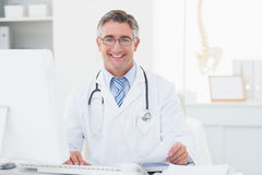 Happy male doctor reviewing documents at table Royalty Free Stock Photo