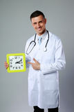 Happy male doctor showing on clock Royalty Free Stock Images