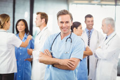 Happy male doctor standing with arms crossed. Portrait of happy male doctor standing with arms crossed and colleagues standing behind and discussing in hospital Stock Photography