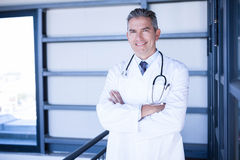 Happy male doctor standing with arms crossed. Portrait of happy male doctor standing with arms crossed in hospital Stock Images