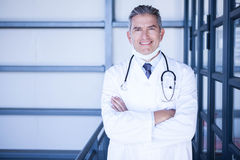 Happy male doctor standing with arms crossed Royalty Free Stock Photo