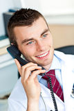 Happy male doctor talking on phone. Sitting in his office Stock Photography