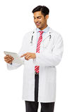 Happy Male Doctor Using Digital Tablet. Happy young male doctor using digital tablet against white background. Vertical shot Stock Images