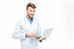 Happy male doctor using laptop computer Stock Photos