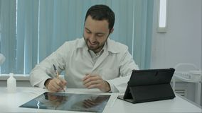 Happy male doctor working at office, writeing, smiling. Happy male doctor working at office, writeing documents at the table, smiling. Tablet and lamp standing Royalty Free Stock Images