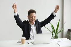 Happy male employee celebrating good online result looking at la. Happy millennial businessman raising hands feeling joy celebrating success or good online royalty free stock photos