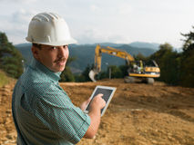 Happy male engineer. Portrait of young caucasian engineer on construction site holding digital tablet Royalty Free Stock Photos