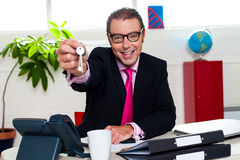 Happy male executive handing over the keys Stock Photography