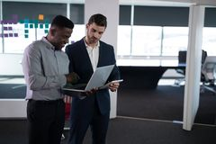 Happy male executives using laptop and digital tablet. In office Stock Photos