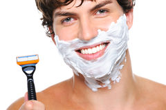 Happy male face with razor over white. Laughing man's face with shaving cream on it and razor near the face Royalty Free Stock Photos