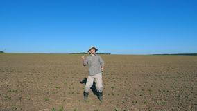 Happy male farmer dances funny among small green sprouts at the field on sunny day. Young man enjoying and having fun on