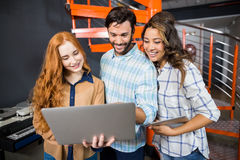 Happy male and female executives using laptop. In office Stock Image