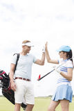 Happy male and female friends giving high-five at golf course Royalty Free Stock Image