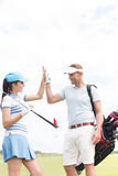 Happy male and female friends giving high-five at golf course Stock Photography