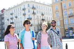 Happy male and female friends walking on city street royalty free stock photography