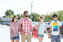 Happy male and female friends walking on city street stock images