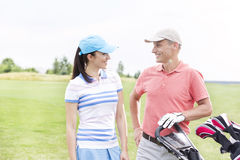 Happy male and female golfers communicating against clear sky Stock Photography