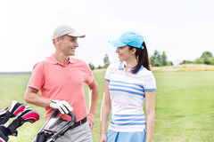 Happy male and female golfers communicating against clear sky Stock Photo