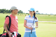 Happy male and female golfers communicating at course Royalty Free Stock Images