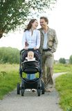 Happy male and female parents walking with their child in baby carriage royalty free stock photos