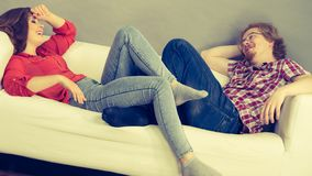 Happy man and woman lying on sofa stock photo