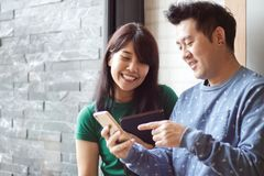 Happy male and female watching funny online video content on mobile phone. Selective focus. Copy space. royalty free stock image