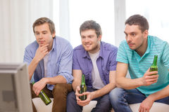 Happy male friends with beer watching tv at home. Friendship, sports and entertainment concept - happy male friends with beer watching tv at home Stock Photo