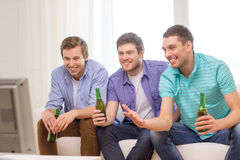 Happy male friends with beer watching tv at home stock photography