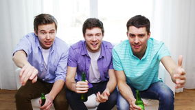 Happy male friends with beer watching tv at home Royalty Free Stock Photos