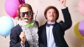 Happy male friends dancing in photo booth. Two happy male friends having fun dancing in photo booth stock footage